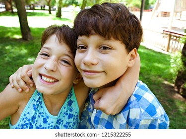 Beautiful naughty brother and sister children hugging squeezing, looking with fun expressions and heads together in sunny park. Kids friends fun outdoors activities, leisure recreation lifestyle.