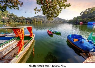 Beautiful Naukuchiatal lake at sunset with tourist paddle boats at Nainital Uttarakhand India.