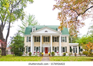 A beautiful neoclassic style mansion with columns along the front of the house. The yard features large trees, grass and bushes.