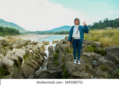 beautiful nepali young girl happy mood showing two fingers over River and amazing Rock background, Seti river Kaski Nepal, 10/22/2019