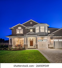 Beautiful New England Style Home Exterior at Night With Green Lawn, Driveway, Covered Porch, and Deep Blue Sky
