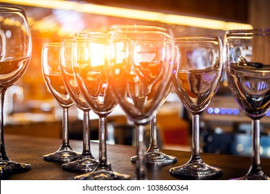 Beautiful new glasses for wine from glass stand in even rows on a wooden table in a restaurant