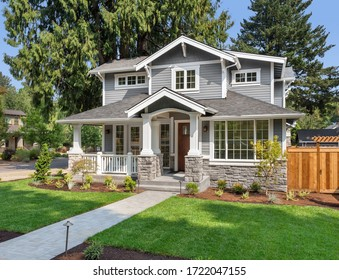 Beautiful new home exterior with covered porch and green grass on bright sunny day with blue sky