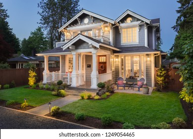 Beautiful New Home Exterior at Night: Home with Green Grass and Covered Porch, including Stately Gables and Columns.
