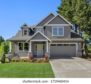 Beautiful new home exterior with two car garage and covered porch on sunny day