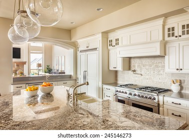Beautiful New Kitchen Interior with Island, Sink, Cabinets and Pendant Lights in New Home