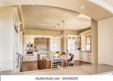 Beautiful New Kitchen with Island, Sink, Cabinets, and Hardwood Floors in New Home