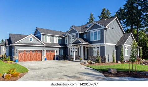 Beautiful new luxury home exterior. Traditional home in suburban neighborhood with three car garage, two stories, and columns in entry.