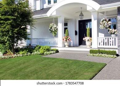 Schöne neue Luxus-Haus Außenfassade im Sommer. Individuelles Haus mit Veranda und professioneller Landschaft in Kanada.