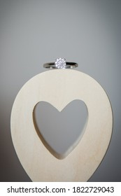 Beautiful new shiny white gold engagement ring with shiny diamond, placed on the wooden ampersand sign with heart shape hole cut, plain background