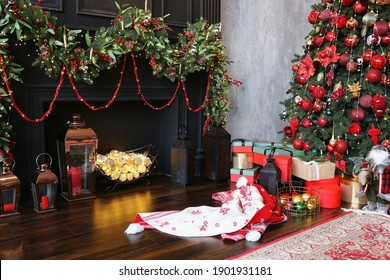 beautiful New Year tree decorated with red and gold toys against a gray concrete wall in a luxury apartment