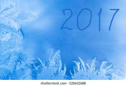 Beautiful New Year winter background (frozen window as a winter background with 2017 written on it)