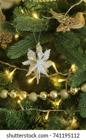 Beautiful new year's golden toys on the branch of the pine. Christmas decorated Christmas tree.