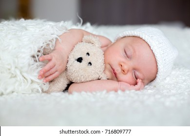 Beautiful newborn baby boy, sleeping with little toy