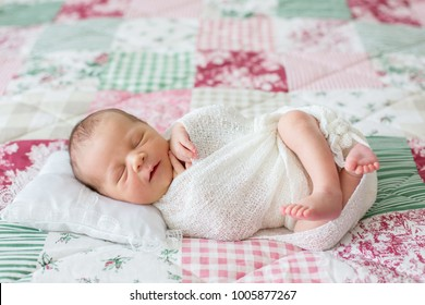 Beautiful newborn baby boy, widely smiling, wrapped in wrap, lying down in bed, peacefully sleeping. Infant sleep in bed. Healthy little kid shortly after birth. Happy baby