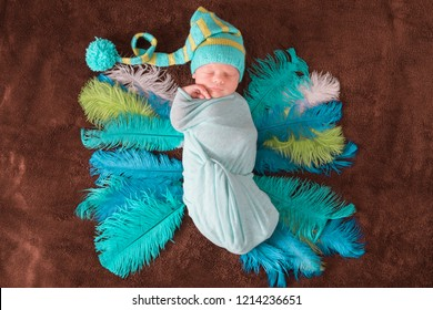 Beautiful newborn baby cute sleeping in a knitted dwarf cap with a pompon and wings of ostrich feathers wrapped with a blue diaper. The first days of a child's life. Mother care