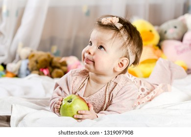 Beautiful newborn baby girl with apple, lying in her bed and smiling.
