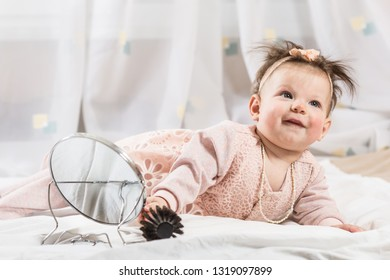 Beautiful newborn baby girl with hairbrush, lying in her bed and smiling.