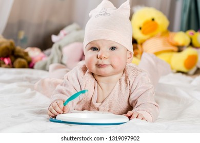 Beautiful newborn baby girl with hat, lying in her bed and smiling.