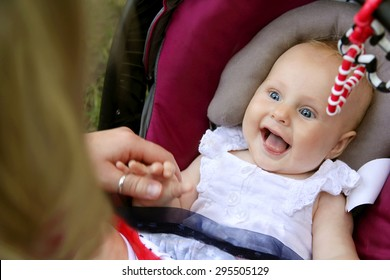 A beautiful newborn baby girl is laughing and sticking out her tongue as her mother holds her hands while she sits in her car seat.