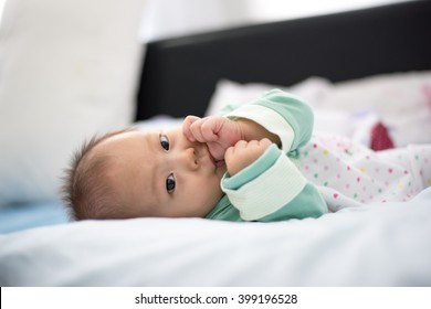 beautiful newborn baby girl is laying down on a blanket looking at the camera as she is sucking her thumb