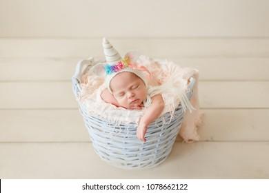 Beautiful newborn baby girl in A unicorn hat sleeping in a wicker basket in props on a wooden beige floor