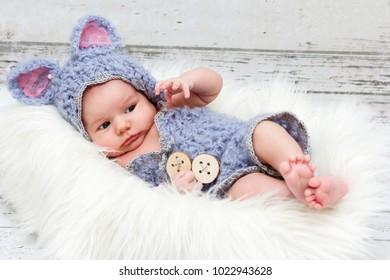 Beautiful newborn baby girl wearing knitted costume lying on the fur