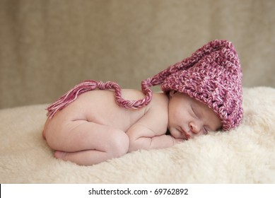 A beautiful newborn baby girl wearing a hat, soft focus