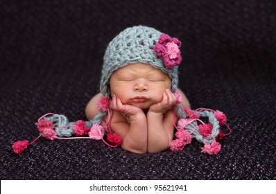 Beautiful newborn baby resting on her elbows and hands