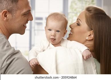 Beautiful newborn baby sticking tongue, parents smiling.