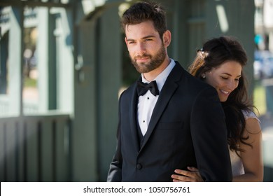 Beautiful newlywed couple dressed sharp and stylish, smiling together outdoors