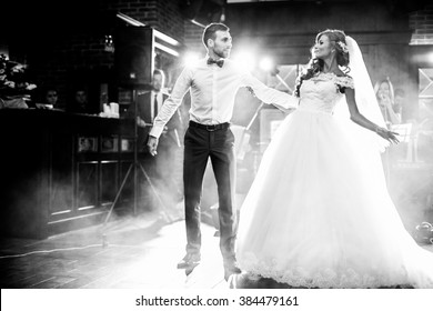 Beautiful newlywed couple first dance at wedding reception surrounded by smoke and lights b&w