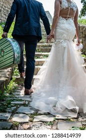 Beautiful newlywed couple are walking away climbing the stone stairs with old fashioned suitcase.