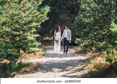 Beautiful newlyweds couple walking in the woods. The bride and groom are walking.