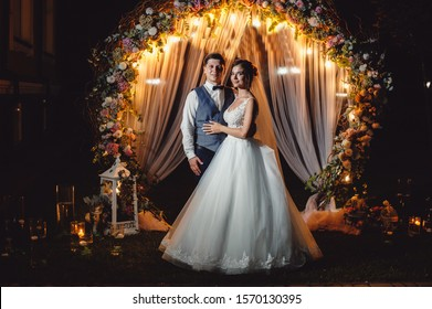 Beautiful newlyweds hugging against the backdrop of flowers and green arch with lamps and candles. Wedding portrait of a stylish groom and bride on a background of a wedding photo zone. Film noise.