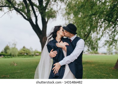 Beautiful newlyweds are hugging against the background of green grass and willows in the park and garden. Wedding portrait of a stylish groom in a hat and a beautiful bride with curly hair in a dress.