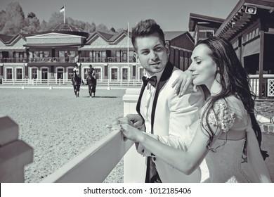 Beautiful newlyweds on a horses farm celebrating wedding in spring nature