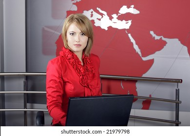 beautiful news TV Presenter in front of the laptop and looking at the camera