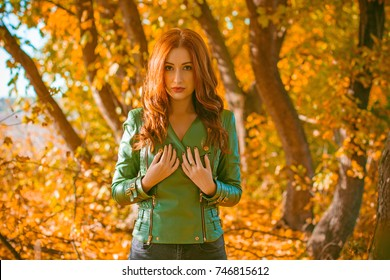 Beautiful and nice red-haired lady, looks stylish, dressed in a green leather jacket and black jeans.