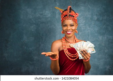 beautiful nigerian lady wearing edo bridal costume holding some money in one hand and stretching out the other towards the viewers and smiling