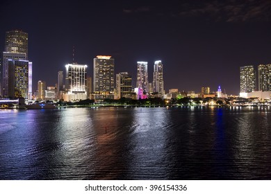 Beautiful night aerial view of Miami Beach, boat and skycrappers, downtown skyline illuminated with bright lighting