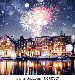 Beautiful night in Amsterdam. Night illumination of buildings and boats near the water in the canal. Photo greeting card. Colorful fireworks on the black sky background