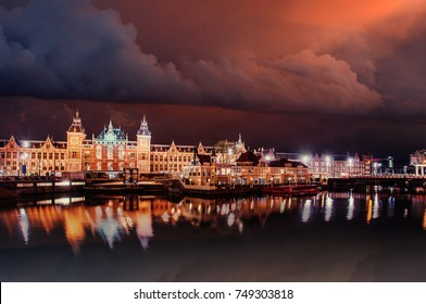 Beautiful night in Amsterdam. Night illumination of buildings and boats near the water in the canal. Dramatic sky.