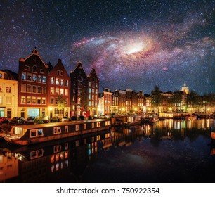 Beautiful night in Amsterdam. Night illumination of buildings and boats near the water in the canal. Courtesy of NASA.