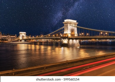 Beautiful night Budapest, the Chain bridge (Szechenyi lanchid) across the Danube river in lights and starry sky, cityscape suitable for cover or desktop background
