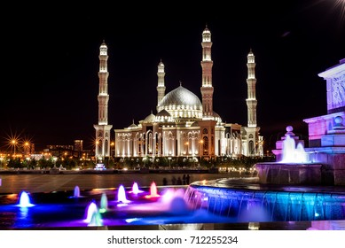 A beautiful night city in a summer night. This photo opens a view of the Moslim mosque of our city. Fountains in the city are shimmered at night with incredible colors. Kazakhstan. Astana.