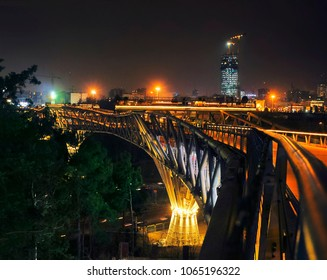 Beautiful night city view - Tabiat steel bridge decorated with bright illumination connects two public parks against the background of dark sky and distant skyscraper, Tehran, Iran, Western Asia.