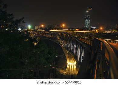 Beautiful night city view - Tabiat steel bridge decorated with bright illumination in public park at the background of dark sky and distant skyscraper in northern Tehran, Iran, Western Asia.