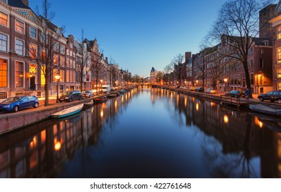 Beautiful night cityscape in Amsterdam, Netherlands. Reflected city lights in water with blue sky. Night illumination of buildings and boats near the water in the canal. Wonderful view on houses