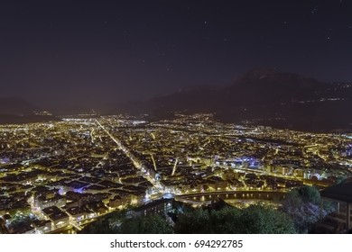 Beautiful night cityscape of Grenoble in the Rhone-Alps, France, seen from the top of the hill. Nightlife at streets full of lights with gorgeous mountains in the background under the stars